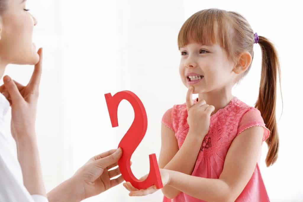 Kind übt die Aussprache eines Buchstabens